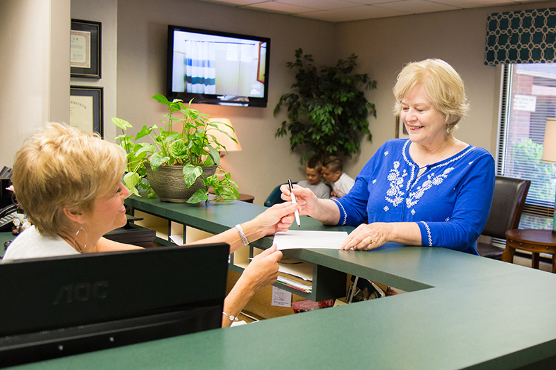 Patient signing forms at Jon C. Packman DDS Office Tour