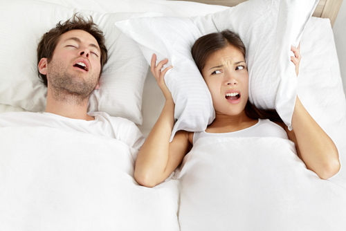 Snoring man in bed needs sleep apnea treatment from Jon C. Packman DDS